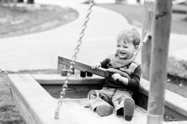 A boy steers a wooden boat in a family photo shoot.