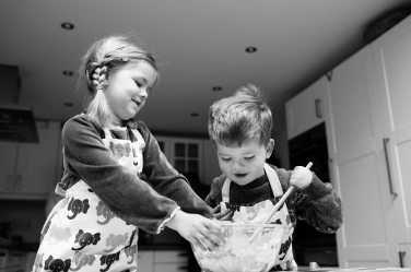 A brother and sister cook in the kitchen.