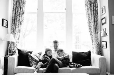 A mother and two children sit on the sofa to read stories.