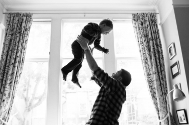 A father throws his son into the air while they are playing.
