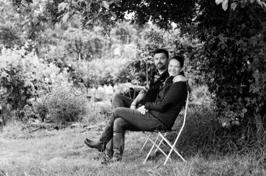 A mum and dad sit on chairs in their vegetable garden.