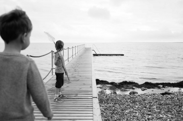 A girl takes a net onto the jetty to see what she can catch.