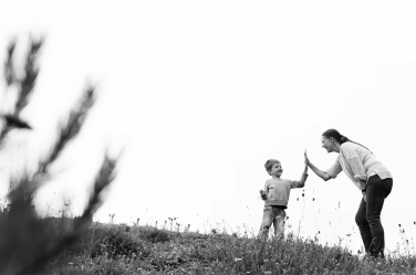 A mother and son high five each other.