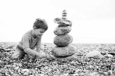 A boy balances rocks on the beach.