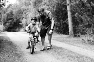 A father sends his son off on his bike.