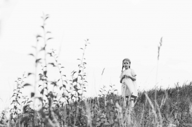 A black and white portrait of a girl in a field.