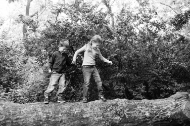A brother and sister walk along a large log.