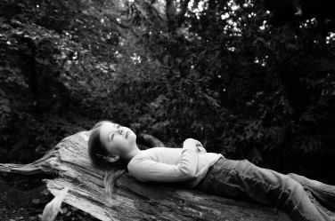 A sister lies on a log for a black and white portrait.
