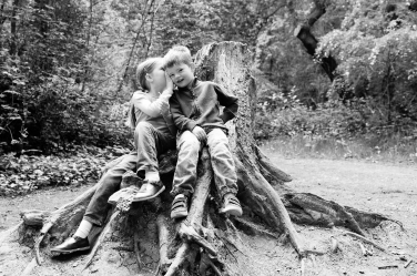 A brother and sister perch on a tree stump while the sister whispers a secret to the brother.