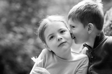 A tiny boy whispers a secret to his patient older sister.