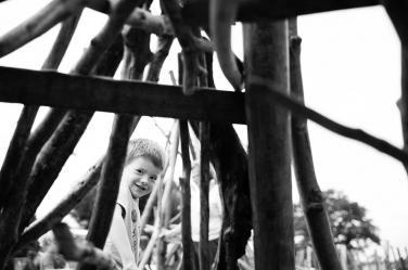 A boy peers through a wooden den during a family portrait shoot.