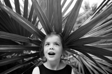 A green palm leaf makes a simple hat for this black and white girls portrait.