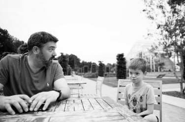Father and son sit at a wooden table together.