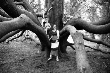 A family portrait in the surrounds of a large old tree.