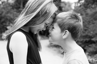 A brother and sister look each other in the eye during this black and white photo.