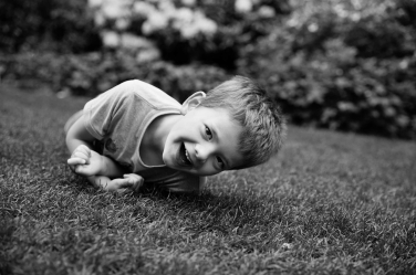 A boy rolls around on the grass during a family photo shoot.