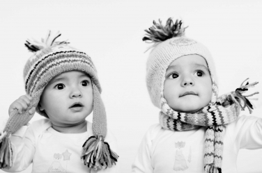 Two children in woolly hats to ward off winter chills and make for a cosy sibling portrait.