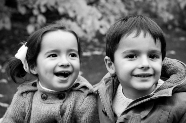 A brother and sister as toddlers in a black and white lifestyle portrait.