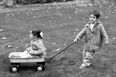 A brother drags his sister along in family portraits.
