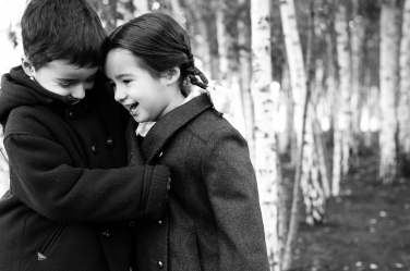 A brother and sister cosy into each other during a winter shoot with birch trees in the background.