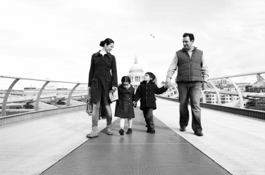A mother, father and two children walk along the Millennium Bridge with St Paul's in the background.