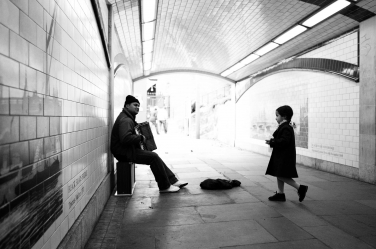 A girl gives change to a busker during a family portrait shoot on London's south bank.