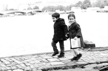 A brother and sister walk along the Thames together during a London portrait shoot by professional photographer Helen Bartlett.