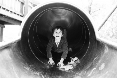 A boy arrives at the end of a metal slide in south London.