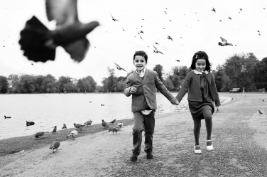 A brother and sister scare away a flock of pigeons during a black and white portrait shoot.