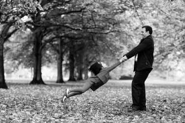 A father swings his daughter around during a family portrait session in a London park.