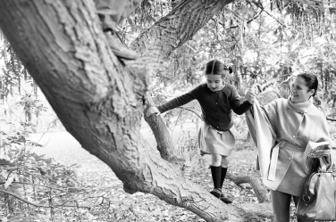 A mother guides her daughter up a tree branch during a family portrait session.