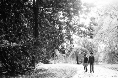 A boy and girl hold hands as they walk through a London park with the light behind them.