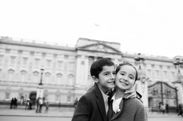 A brother and sister outside the gates of Buckingham Palace during their family portrait shoot.