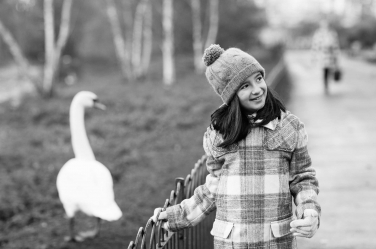 A girl dressed in warm hat and coat meets a swan in one of London's parks.