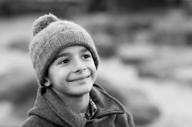 A classic black and white portrait of a boy in winter hat and coat.