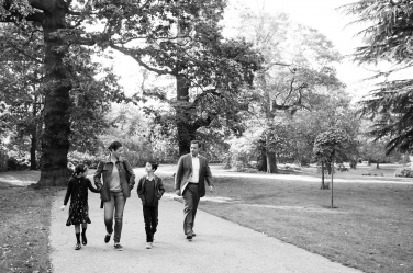 A family walks through the park together during their London portrait shoot.