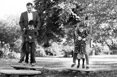A family bouncing on sprung tree cut-offs during their professional photo shoot.