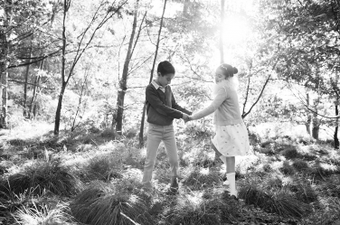A brother and sister hold hands and dance in the park's sunshine.