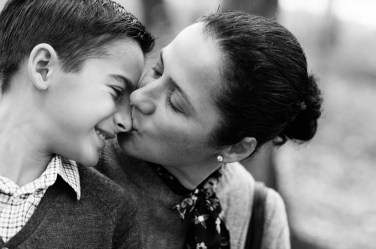 A mother kisses her son during a family photo session.