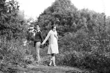 A brother and sister hold hands during a black and white portrait shoot.