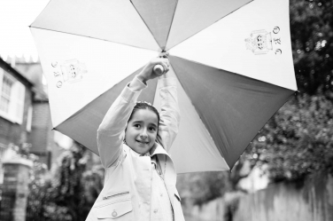 A girl twirls her umbrella during a family photo shoot.