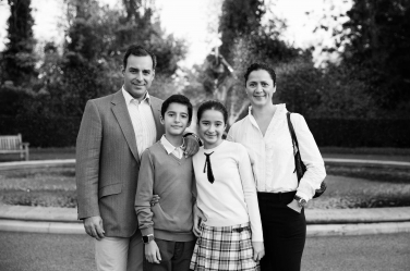 A black and white family portrait with a fountain in the background.