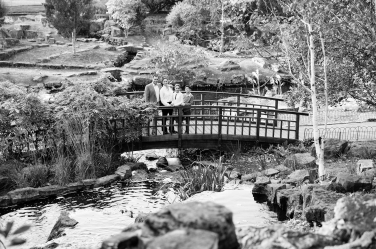 A family stands on a park bridge during their family shoot.