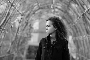 A teenager portrait in front of a outdoor arch. It's part of a professional portrait shoot in London, UK.