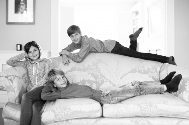Three teenagers slump on a family sofa as part of a casual, lifestyle shoot by London professional photographer Helen Bartlett.