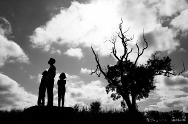 This portrait of a teenager and their two siblings is taken as a strong silhouette by London photographer Helen Bartlett.