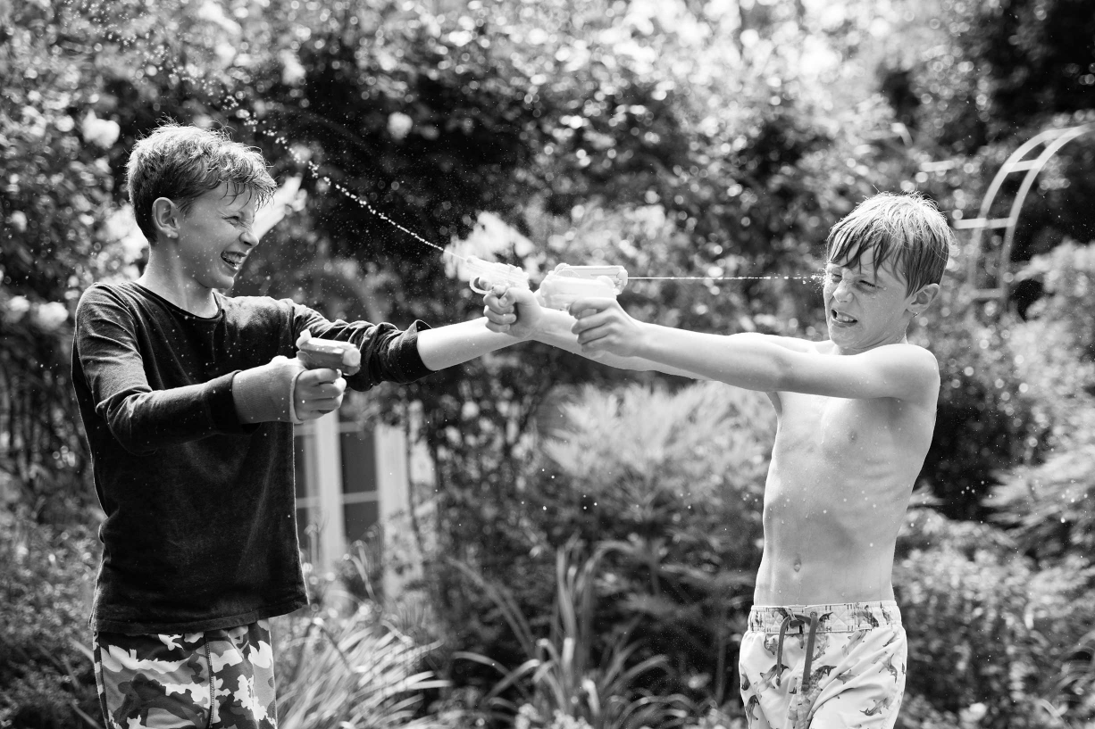Teenage brothers squirt each other with water guns in this summer teen portrait. Photo: Helen Bartlett (London).