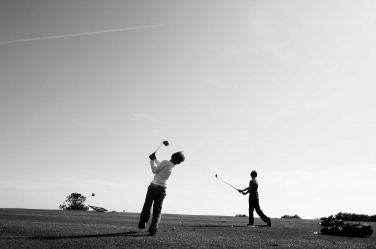 Hobbies such as golf are a great focus for teenage portraits, allowing the personality of the teenager to show through without self-consciousness. This golfing portrait of teenagers it by London photographer Helen Bartlett.