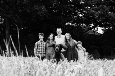 A happy family portrait with teenagers and a spaniel, leaping towards portrait photographer Helen Bartlett.
