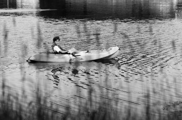 A teenager chills on his paddleboard in this languid family portrait.